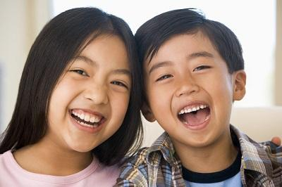 a young boy and girl smiling