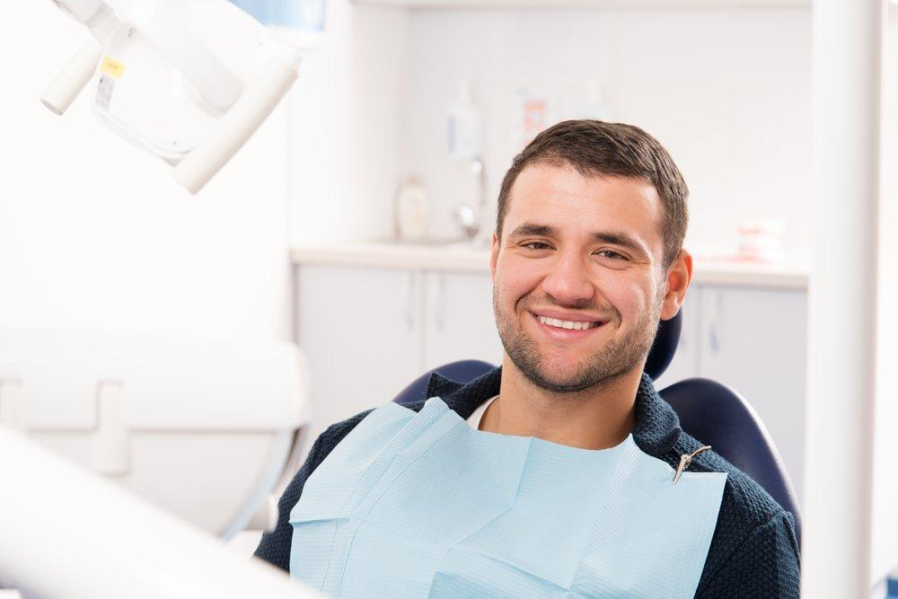 Man smiling while sitting in dental chair