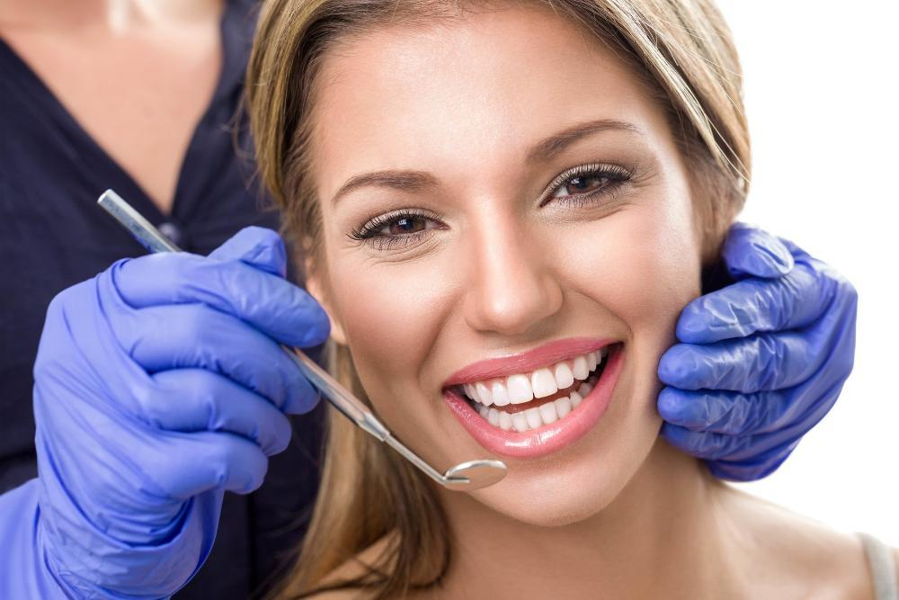 Woman smiling with dentist holding dental mirror near mouth